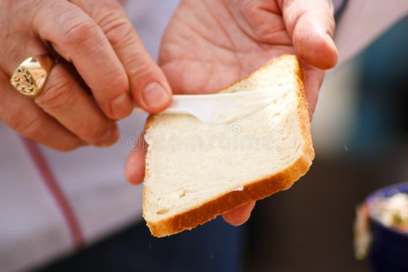 Beurrer une part de pain images libres de droits