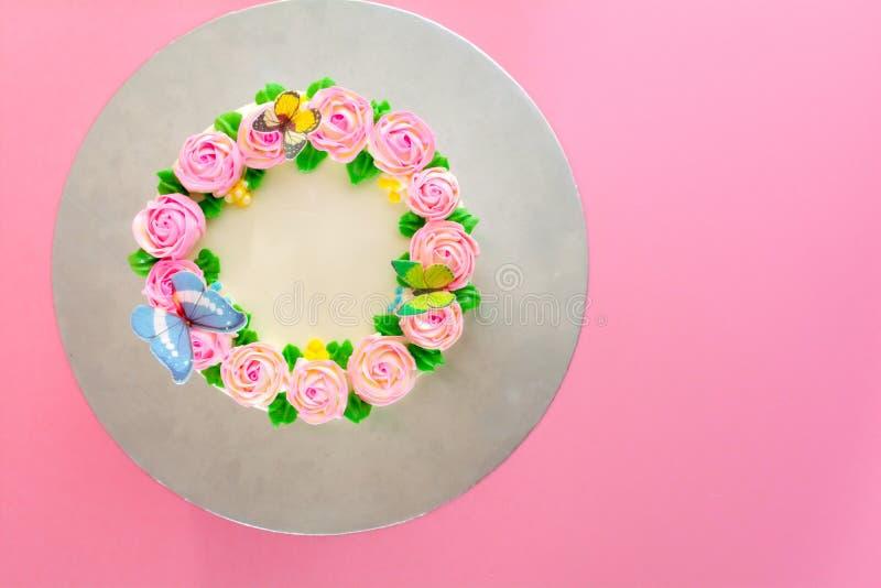 Beurrez la crème du gâteau d'étang de vanille d'oo décoré par roses roses sur le fond rose avec l'espace de copie servi en fête d images stock