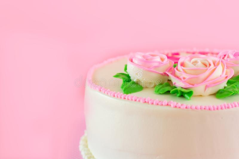 Beurrez la crème du gâteau d'étang de vanille d'oo décoré par roses roses sur le fond rose avec l'espace de copie servi en fête d image stock