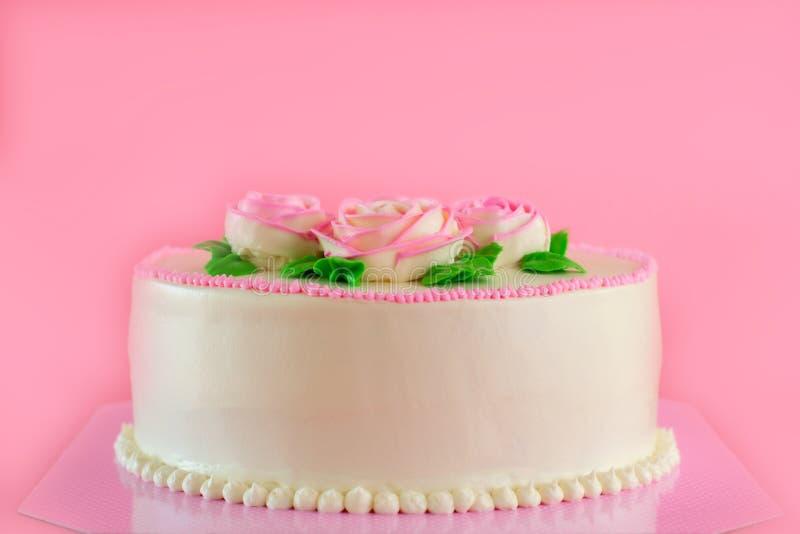 Beurrez la crème du gâteau d'étang de vanille d'oo décoré par roses roses sur le fond rose avec l'espace de copie servi en fête d photos libres de droits