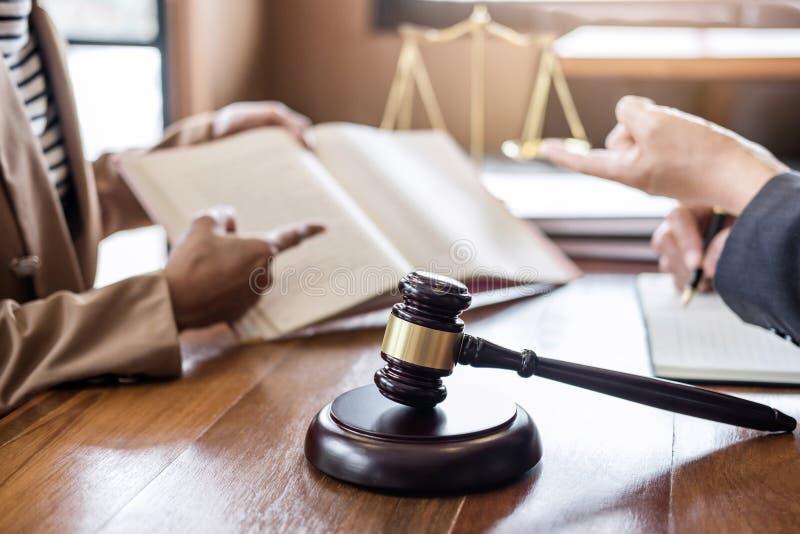 Beurteilen Sie Hammer mit Skalen von Gerechtigkeit, Gesch?ftsfrau und Mannesrechtsanw?lte oder -ratgeber, die Vertragspapiere an  stockfotos