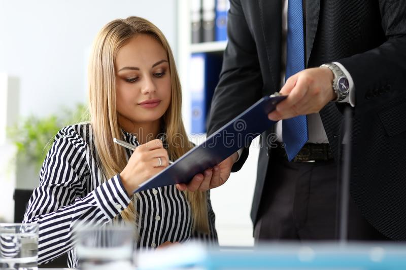 Beutiful thoughtful clerk signing important document. Clipped to pad portrait stock images