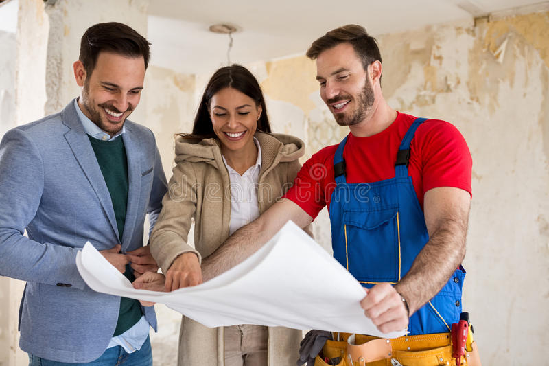 Beutiful young couple looking blueprints of their home with hand stock photography