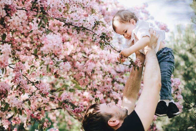 Beutifull weinig jongen in zijn vaderhanden houdt een tak van de kersenbloesem en glimlacht stock foto's