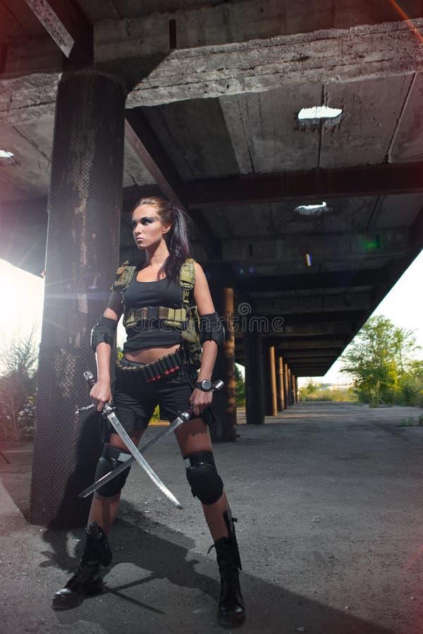 Beväpnad flicka för sexig militär med vapnet royaltyfri foto