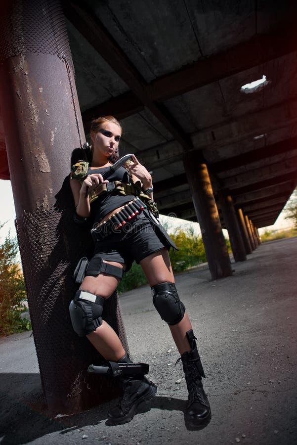 Beväpnad flicka för sexig militär med vapnet royaltyfri fotografi