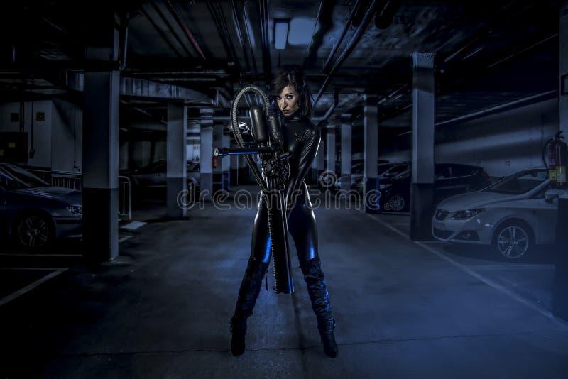 Beväpnad kvinna i ett garage, framtida begrepp, svart latex med neon l arkivfoton