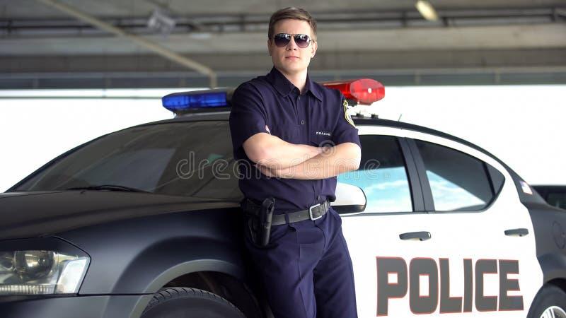Beväpnad polis i solglasögon som står nära patrullautomatiskn, farligt yrke fotografering för bildbyråer