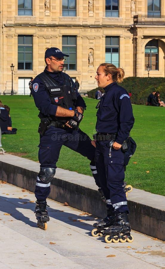 Beväpnade nationell polistjänstemän, man och kvinnlig, på rollerblades som patroling nära Louvre i Paris, Frankrike arkivfoton