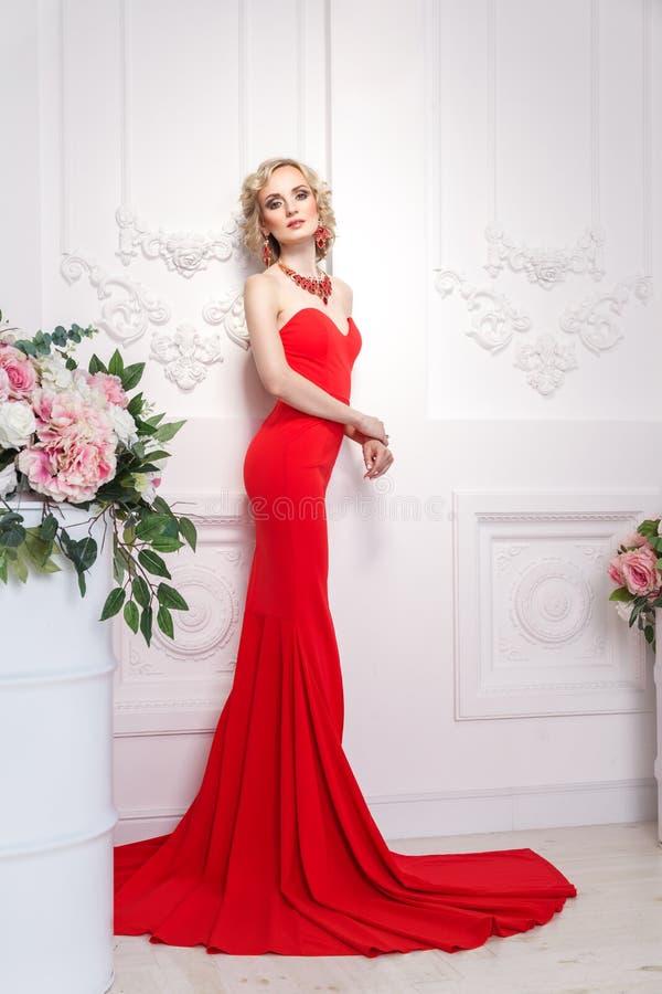 Bevallige jonge volwassen vrouw, met rode lange kleding, juwelen en blo stock foto's