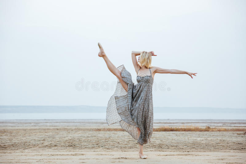 Bevallige jonge vrouwendanser die op het strand dansen stock fotografie