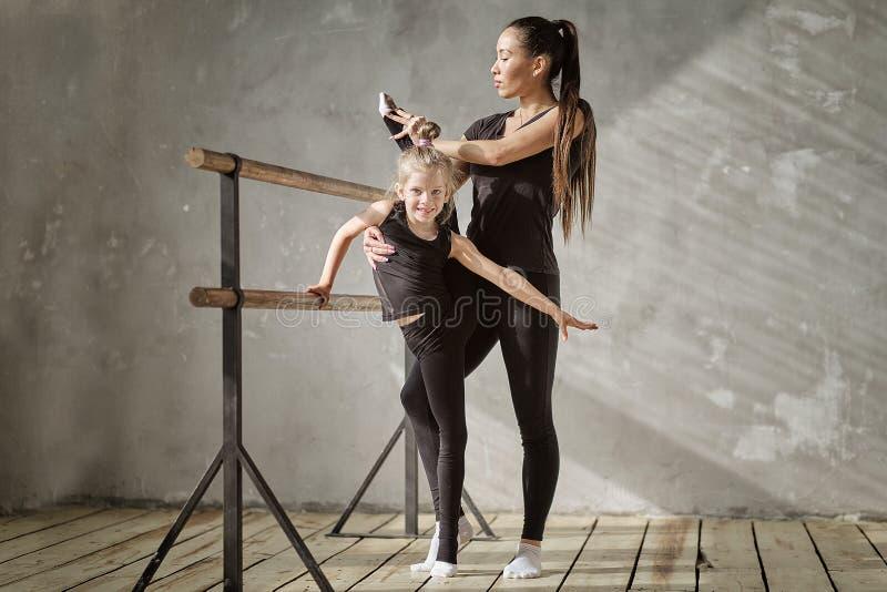 Bevallige meisjeballerina die zich op handen bevinden en zich met leraar in dansstudio uitrekken stock fotografie