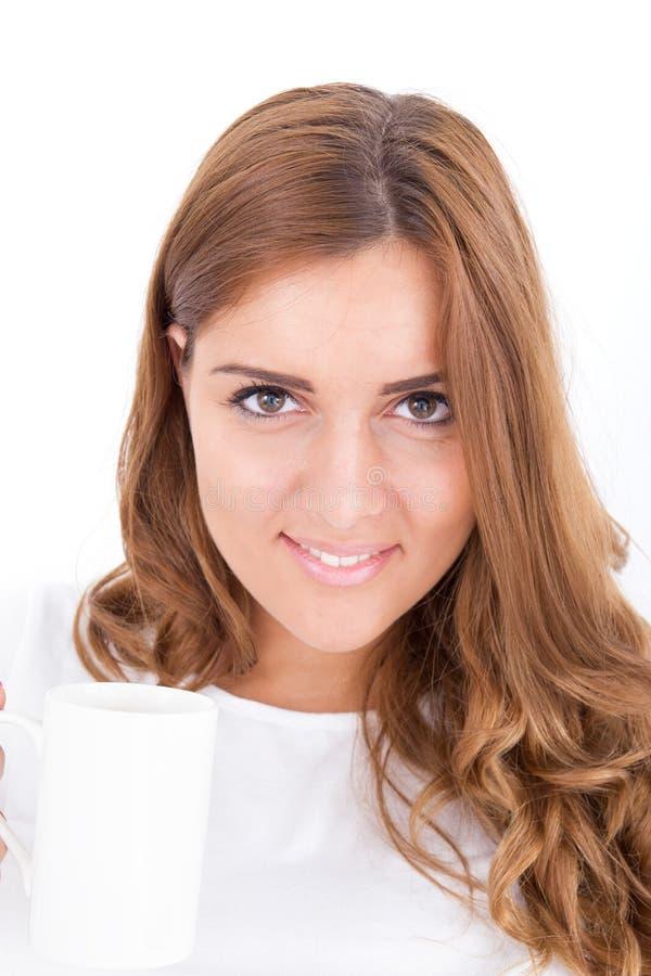 Bevanda bevente della donna castana da una tazza in camera da letto luminosa immagini stock