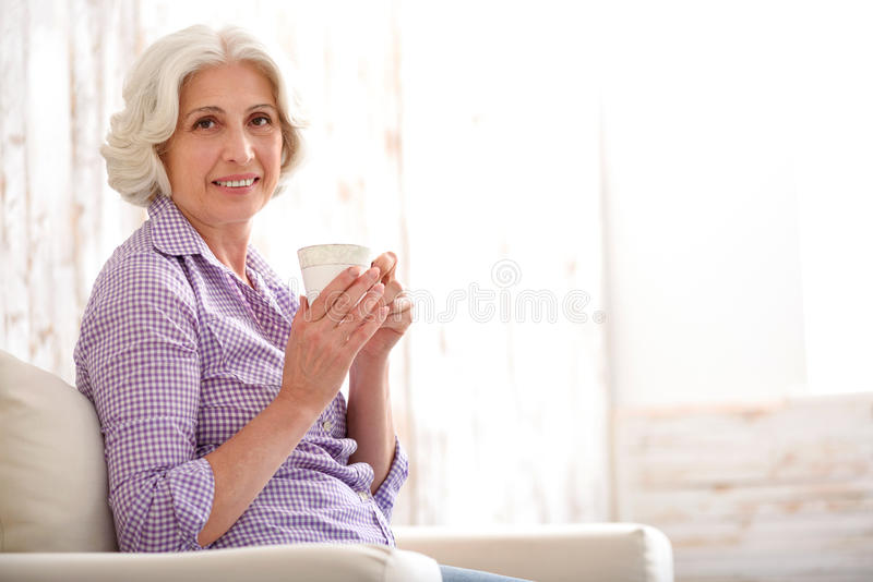 Bevanda bevente felice della donna anziana a casa immagini stock libere da diritti