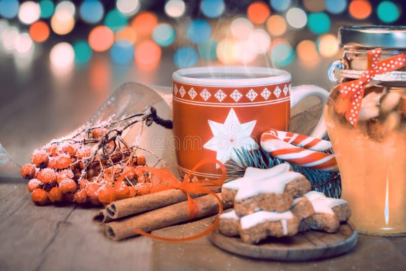 Bevanda, biscotti di Natale e bastoncino di zucchero caldi sulla tavola decorata immagini stock