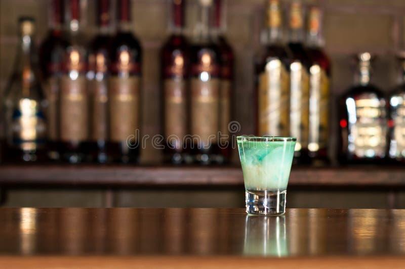 Bevanda blu dell'alcool in chiaro vetro sparato sul contatore di legno con le bottiglie su fondo immagini stock libere da diritti