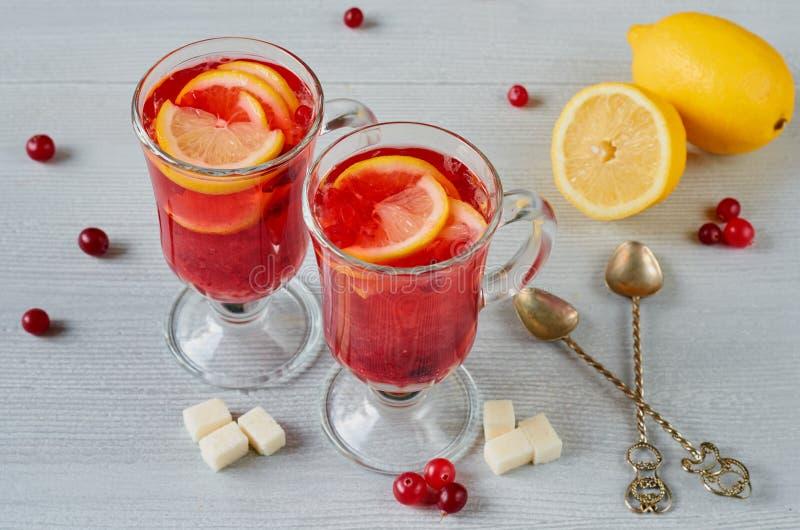 Bevanda calda di inverno - tè o sangria del mirtillo rosso con le fette fresche del limone in vetri sui precedenti concreti grigi fotografia stock