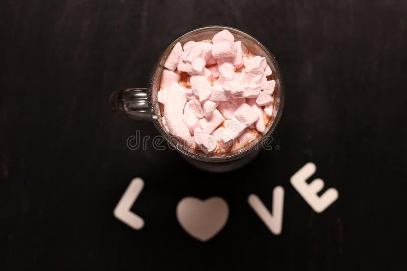 bevanda calda in una tazza di vetro con le caramelle gommosa e molle rosa immagini stock
