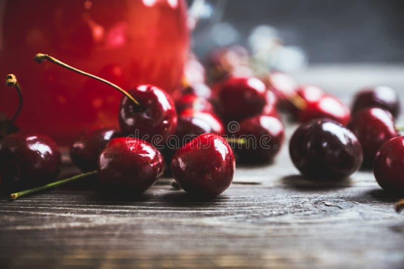 Bevanda casalinga della ciliegia in brocca sui precedenti rustici fotografie stock