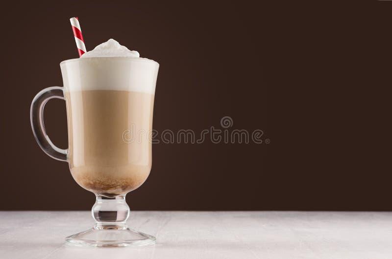 Bevanda del caffè con paglia a strisce rossa e schiuma nell'interno marrone scuro di lusso sulla tavola di legno bianca, spazio d fotografia stock libera da diritti