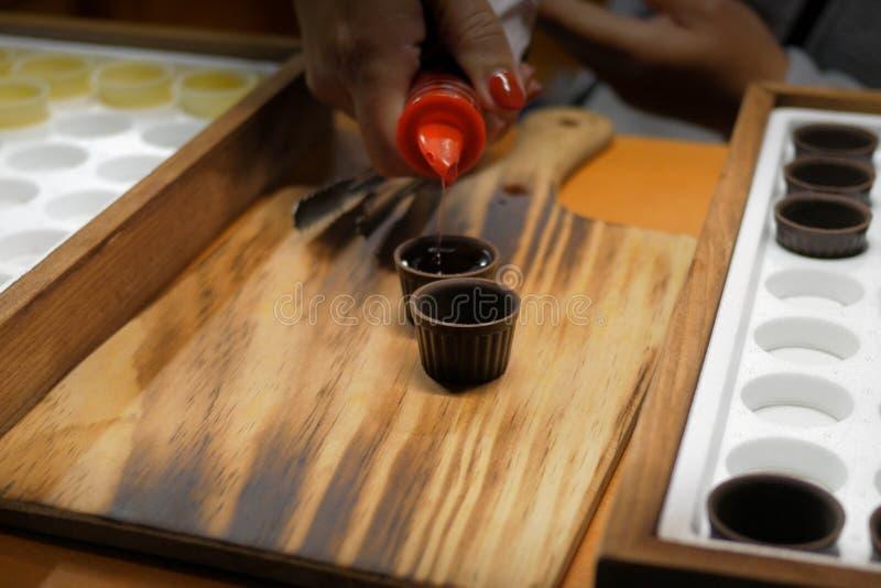 Bevanda del liquore della ciliegia Ginjinha/di Ginja che è versata nelle tazze del cioccolato su fondo di legno Bevanda tradizion fotografia stock libera da diritti