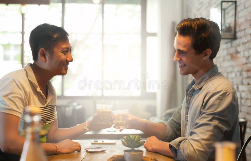 Bevanda del pane tostato di acclamazioni di due uomini, amici asiatici della corsa della miscela immagini stock libere da diritti