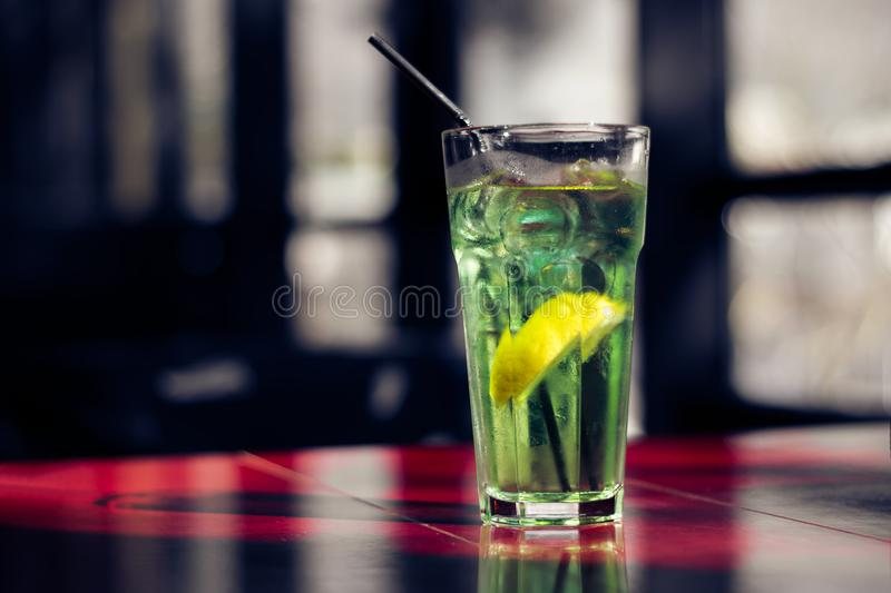 Bevanda deliziosa di estate con una fetta di limone sulla tavola rossa immagine stock libera da diritti