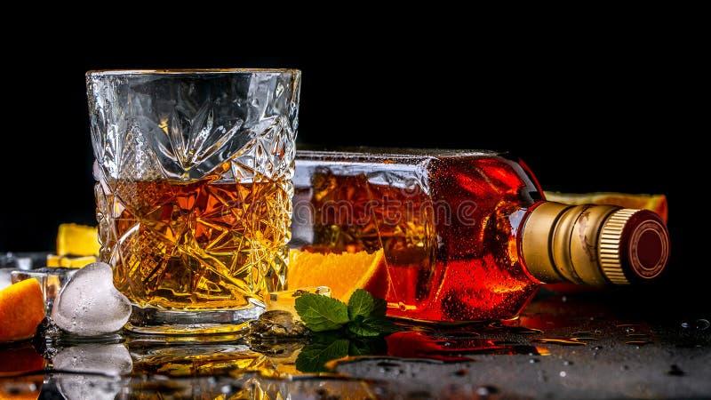 Bevanda dell'elite per rilassamento maschile due vetri di whiskey, di rum e di ghiaccio su fondo nero, spazio della copia bevanda fotografia stock libera da diritti