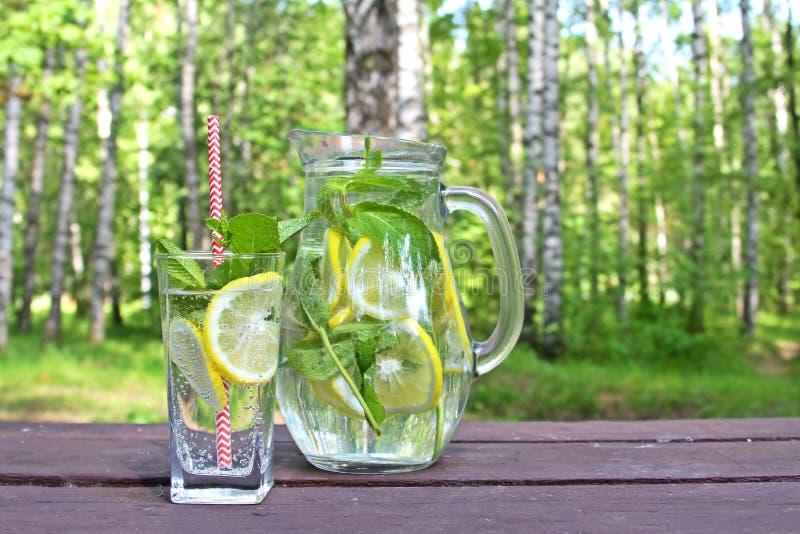 Bevanda della limonata nella brocca di vetro con i limoni, la limetta e la menta sulla tavola di legno all'aperto immagine stock