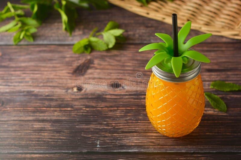Bevanda di estate, vetro del succo di ananas sulla tavola di legno Copi lo spazio immagini stock libere da diritti