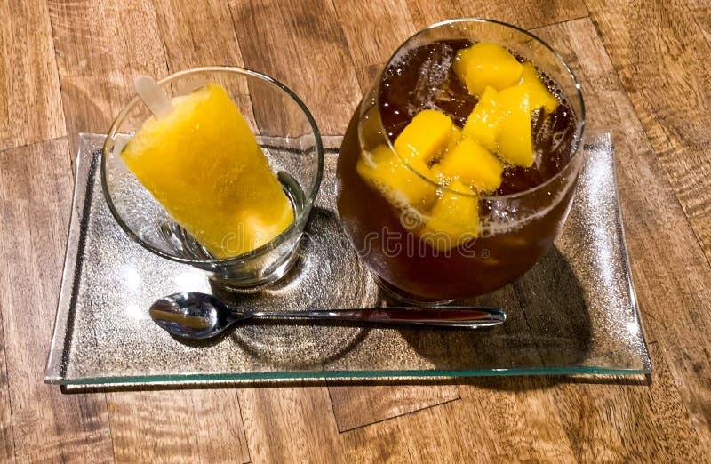 Bevanda di rinfresco della perforazione di frutta in vetro con gelato su fondo di legno immagine stock