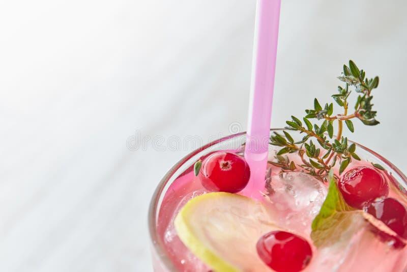 Bevanda di rinfresco di estate con la bacca ed il limone su una tavola di legno leggera Il concetto delle bevande di estate con g immagine stock