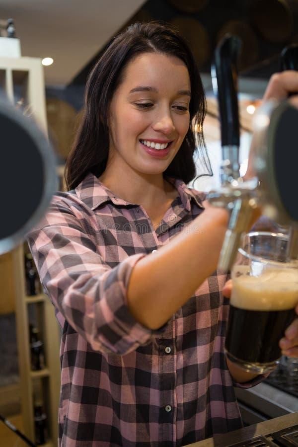 Bevanda di versamento sorridente della giovane cameriera al banco dal rubinetto in vetro immagine stock