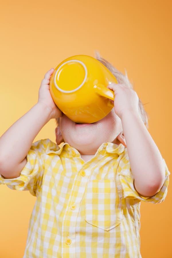 Bevanda divertente del bambino dalla grande tazza gialla fotografia stock