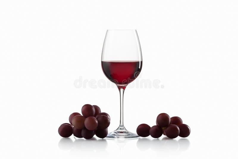 Bevanda ed alimento Bicchiere di vino, con l'isolato dell'uva rossa e del vino rosso fotografia stock