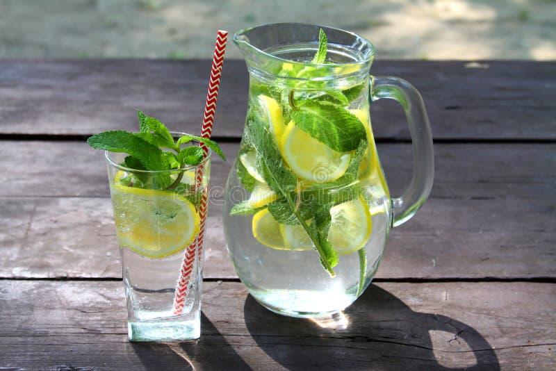 Bevanda fredda della limonata fresca nella brocca di vetro con i limoni, la limetta e la menta sulla tavola di legno all'aperto fotografie stock