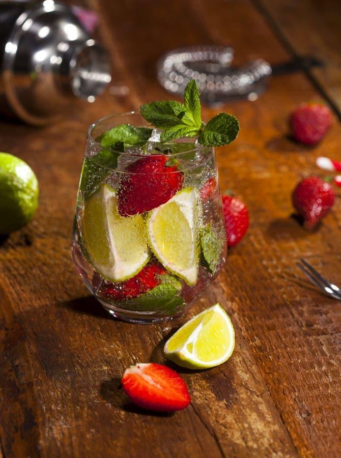 Bevanda fredda di estate con le fragole, la menta, la calce ed il ghiaccio sul contatore di legno della barra Primo piano del coc fotografia stock