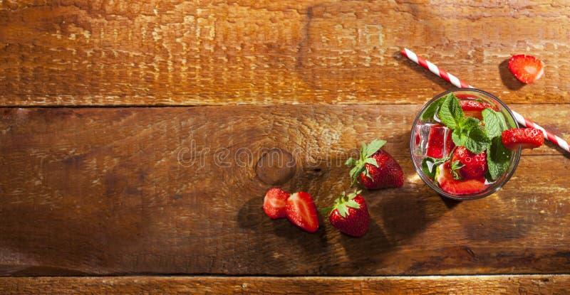 Bevanda fredda di estate con le fragole, la menta ed il ghiaccio in vetro su fondo di legno Primo piano del cocktail con la frutt immagine stock