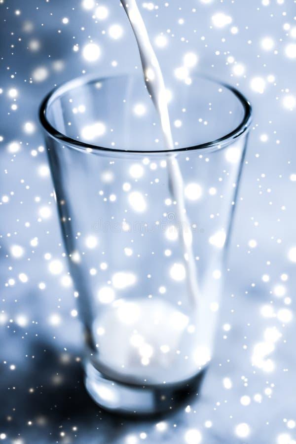 Bevanda magica di festa, latte senza lattosio organico di versamento in vetro sulla tavola di marmo immagine stock