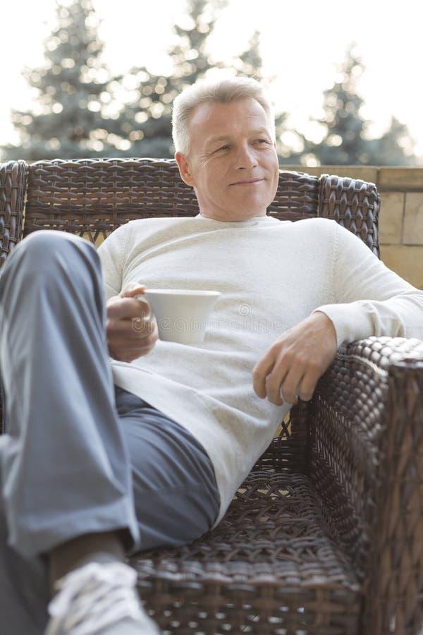 Bevanda matura sorridente della tenuta dell'uomo mentre sedendosi sulla sedia di vimini al patio fotografia stock