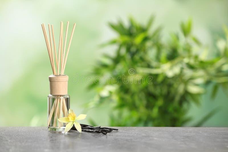 Bevanda rinfrescante di aria di Reed con il fiore ed i bastoni della vaniglia sulla tavola grigia contro fondo verde vago fotografia stock libera da diritti
