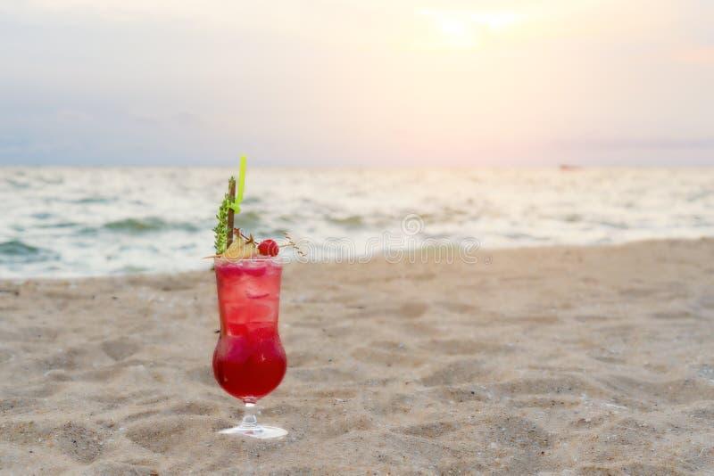 Bevanda rossa del cocktail sulla sabbia in spiaggia nel backgr crepuscolare del cielo & del mare fotografia stock libera da diritti