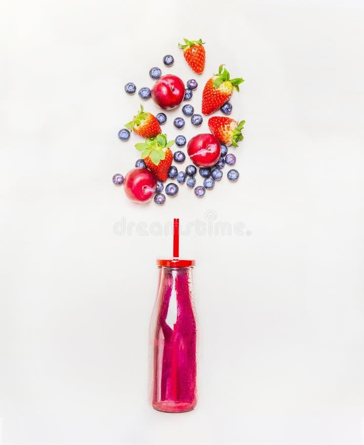 Bevanda rossa del frullato in bottiglia con gli ingredienti delle bacche di frutti e della paglia su fondo di legno bianco immagini stock libere da diritti