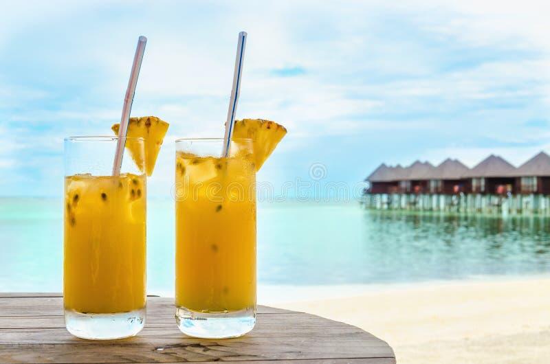Bevande con una paglia su una tavola di legno sui precedenti di una spiaggia sabbiosa e sulle case sull'acqua fotografie stock libere da diritti