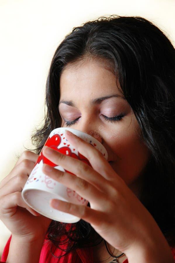 Bevande della donna da una tazza fotografie stock