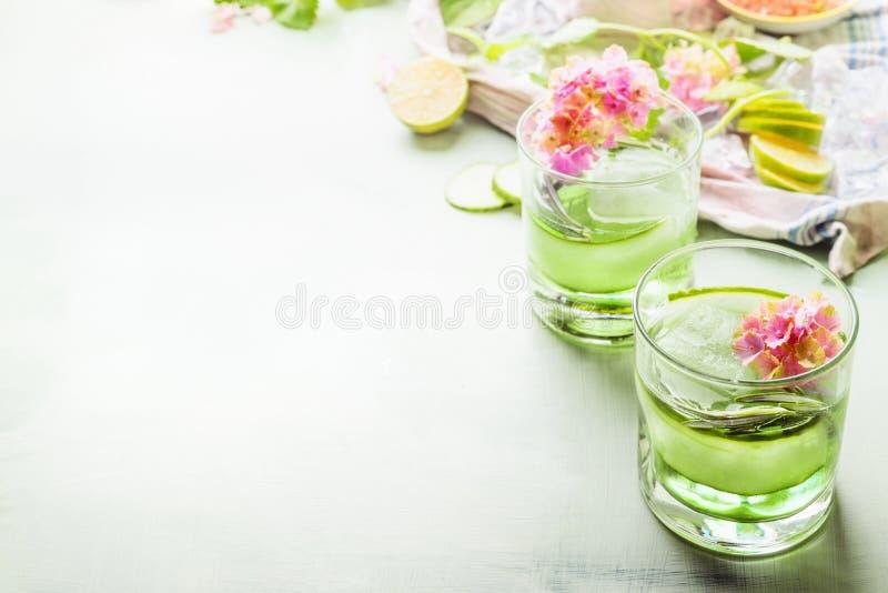 Bevande di rinfresco verdi di estate con ghiaccio in vetri sulla tavola leggera con gli ingredienti ed i fiori Limonata ghiacciat immagine stock libera da diritti