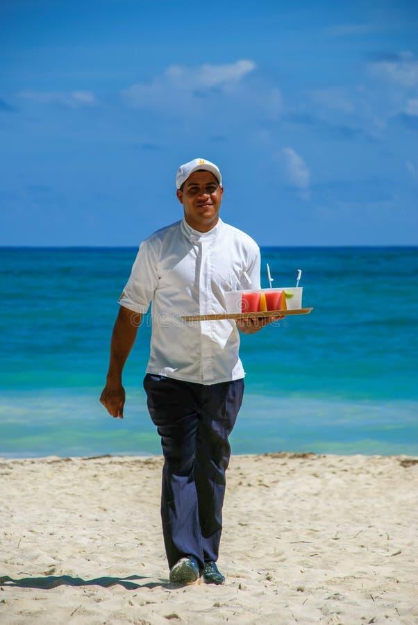 Bevande di trasporto di freddo del cameriere sulla spiaggia immagine stock libera da diritti