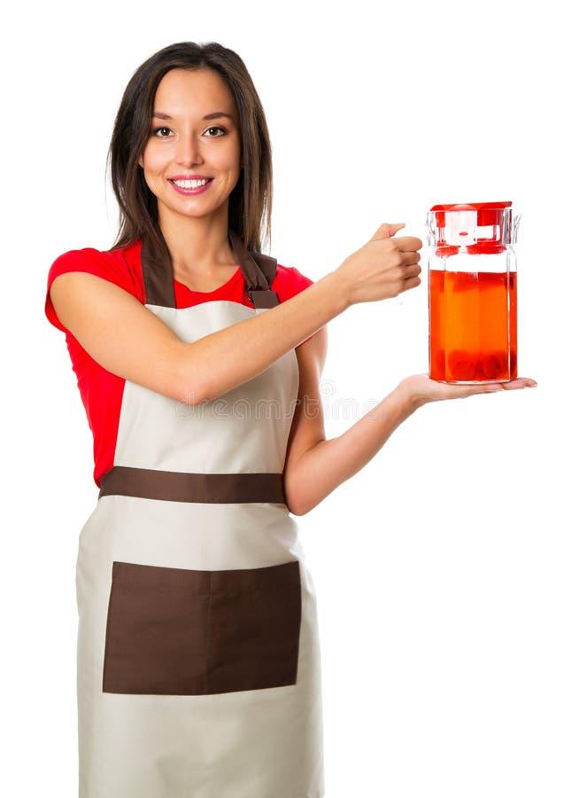 Bevande di versamento della donna allegra con i frutti alla cucina immagine stock