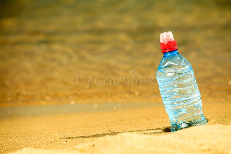 Bevarage ποτό μπουκαλιών νερό σε μια αμμώδη παραλία στοκ εικόνες