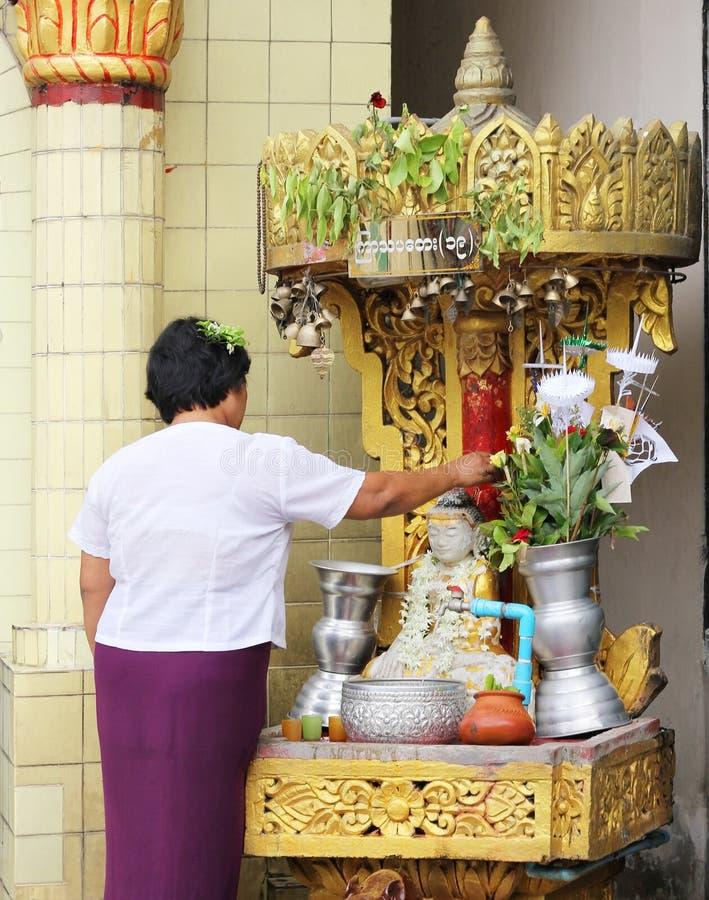 Bevattna att hälla till Buddhastatyn i den Songkran festivalen royaltyfri bild